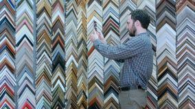 Ung manlig klient som söker efter en ram, välja som tar fotoet med den digitala minnestavlan i atelier Royaltyfri Bild