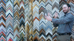 Ung manlig klient som tar selfie med den digitala minnestavlan i ramatelier Arkivfoto