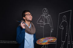 Ung manlig konstnär som målar en kvinna arkivfoto