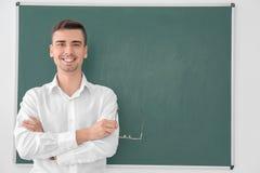 Ung manlig lärare som står den near svart tavla fotografering för bildbyråer