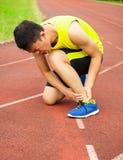 Ung manlig löpare med ankelskada på spår royaltyfria foton