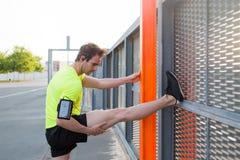 Ung manlig löpare som sträcker benet, innan att jogga utomhus, medan lyssna till musik i hörlurar på hans smarta telefon fotografering för bildbyråer