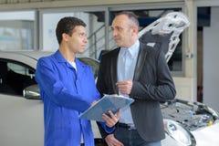Ung manlig mekaniker som talar för att mogna den manliga kunden arkivbild