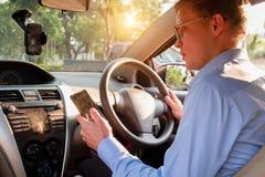 Ung manlig mobiltelefon för bruk för taxichaufför som accepterar kunden i ap royaltyfria foton