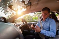 Ung manlig mobiltelefon för bruk för taxichaufför som accepterar kunden i ap royaltyfri foto
