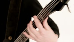 Ung manlig musiker i svart kläder med en svart elbas på en vit bakgrund Uttrycksfull musik för elbasspelare stock video