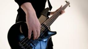 Ung manlig musiker i svart kl?der med en svart elbas p? en vit bakgrund Uttrycksfull musik f?r elbasspelare arkivfilmer