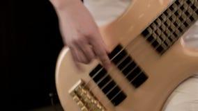 Ung manlig musiker i vit kl?der med en beige elbas p? en svart bakgrund Uttrycksfull musik f?r elbasspelare arkivfilmer