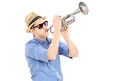 Ung manlig musiker som blåser in i en trumpet Royaltyfria Bilder