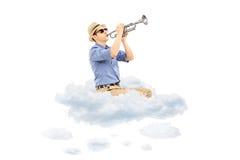 Ung manlig musiker som spelar en trumpet på moln Royaltyfri Fotografi