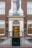 Ung manlig portvakt på hotellingången av berömda Waldorf Astoria i Amsterdam royaltyfria bilder