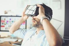 Ung manlig programvaruprogrammerare som i regeringsställning testar en ny app med exponeringsglas för virtuell verklighet 3d Arkivfoton