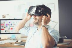 Ung manlig programvaruprogrammerare som i regeringsställning testar en ny app med exponeringsglas för virtuell verklighet 3d Royaltyfri Foto