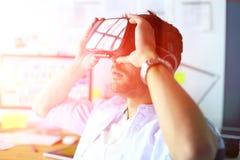 Ung manlig programvaruprogrammerare som i regeringsställning testar en ny app med exponeringsglas för virtuell verklighet 3d Royaltyfria Bilder