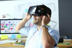 Ung manlig programvaruprogrammerare som i regeringsställning testar en ny app med exponeringsglas för virtuell verklighet 3d Royaltyfri Bild