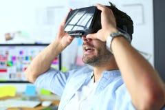 Ung manlig programvaruprogrammerare som i regeringsställning testar en ny app med exponeringsglas för virtuell verklighet 3d Arkivbilder