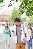 Ung manlig student som använder mobiltelefonen med vänner i bakgrund på gatan royaltyfria foton