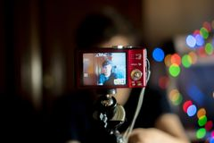 Ung manlig tonåring som hemma gör en blogg med kameran, vlogskytte f royaltyfria bilder