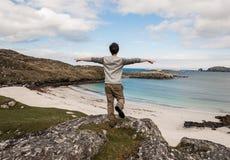 Ung manlig turist med öppna armar som beundrar en vit strand för öken Arkivfoton