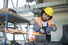Ung manuell arbetare i skyddande workwearklippmetall i bransch Royaltyfri Foto
