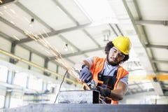 Ung manuell arbetare som använder molar på metall i fabrik Royaltyfri Foto