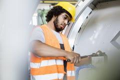 Ung manuell arbetare som drar åt bultar på maskineri i fabrik Royaltyfri Foto