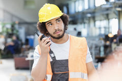 Ung manuell arbetare som lyssnar till walkie-talkie, medan se upp i metallbransch royaltyfria foton