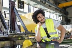 Ung manuell arbetare som talar på mobiltelefonen i metallbransch royaltyfri foto