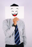 Ung maskering för affärsmanWearing skratt som isoleras på vit Royaltyfria Bilder