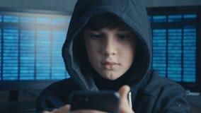 Ung med huva en hackerunge som använder en smartphoneapparat för att kapa Snillepojkeunder hackar systemet på cyberspace lager videofilmer