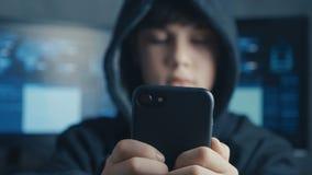 Ung med huva pojke som använder en smartphoneapparat Ståenden av snillepojkeunder hackar systemet på cyberspace stock video