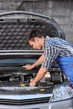 Ung mekaniker i overaller som undersöker en bil Arkivfoto