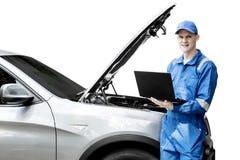 Ung mekaniker med den brutna bilen och bärbara datorn arkivfoton