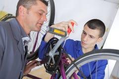Ung mekaniker som arbetar på cykeln under övervakning arkivfoton