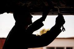 Ung mekaniker som fixar en bil royaltyfri bild