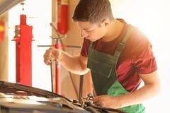 Ung mekaniker som kontrollerar motoroljanivån i bilservicemitt arkivfoto