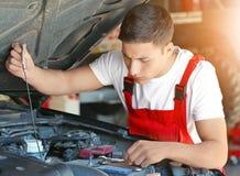 Ung mekaniker som kontrollerar motoroljanivån i bilservicemitt royaltyfri foto