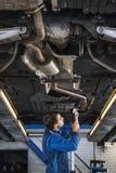 Ung mekaniker som reparerar avgasröret av en bil Arkivfoto