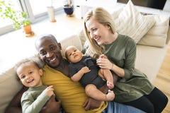 Ung mellan skilda raser familj med hemmastadda små barn royaltyfri foto