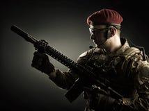 Ung militär man i italiensk kamouflage som rymmer det automatiska geväret Arkivfoton