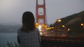 Ung millennial studentflicka för tillbaka sikt som bara står i den mörka sommaraftonen som håller ögonen på iconic Golden gate br arkivfilmer