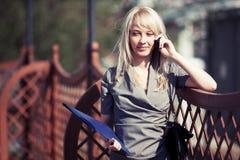 Ung modeaffärskvinna med en mapp som kallar på telefonen Royaltyfri Fotografi