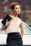 Ung modeaffärskvinna med handväskan bredvid hennes bil Royaltyfri Foto