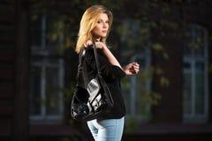 Ung modeaffärskvinna med handväskan som går i nattgata Royaltyfri Foto