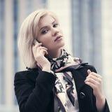 Ung modeaffärskvinna som talar på mobiltelefonen som går i stadsgata Royaltyfri Bild