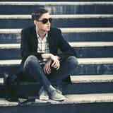 Ung modeaffärsman i solglasögon som sitter på momenten arkivfoto