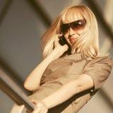 Ung modeaff?rskvinna i solglas?gon som kallar p? mobiltelefonen arkivfoton