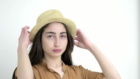 Ung modellflicka i vit bakgrund för studio slut upp härlig caucasian dam i hattblickar på kameran lager videofilmer