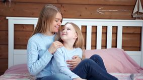 Ung moder för lycklig familj och gullig liten dotter som hemma ler och kramar sammanträde på säng lager videofilmer