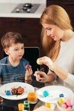 Ung moder för lycklig påsk och hennes lilla ägg för sonmålningpåsk arkivbild